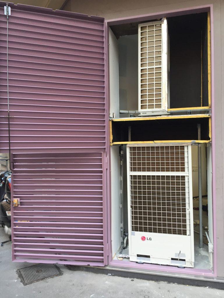 Installation de deux climatisations en ville cachée derrière une grille pare pluie.